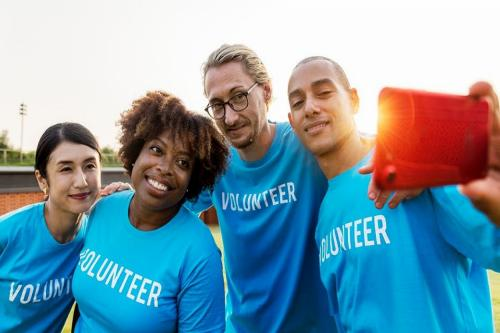 """2 Women and 2 Men taking a picture wearing blue shirts that say """"Volunteer"""""""